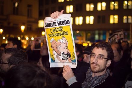 """Manifestante con una portada de Charlie Hebdo """"El amor es más fuerte que el odio""""."""